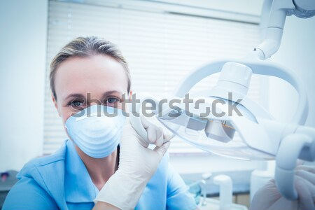 Dentist in blue scrubs holding tools looking at camera Stock photo © wavebreak_media