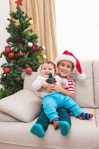 Cute boy and baby brother on couch at christmas Stock photo © wavebreak_media