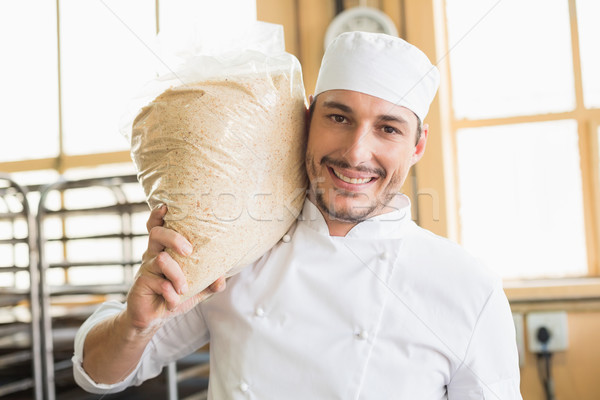 Smiling baker holding bag of rising dough Stock photo © wavebreak_media
