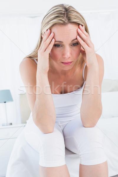Pretty blonde sitting on bed getting headache Stock photo © wavebreak_media