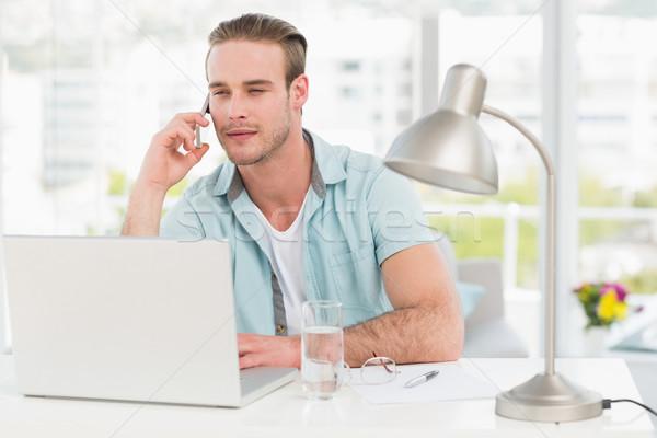 Focused businessman on the phone while using laptop Stock photo © wavebreak_media