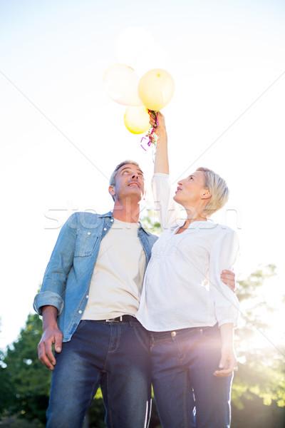 Cute couple holding up balloons at the park  Stock photo © wavebreak_media