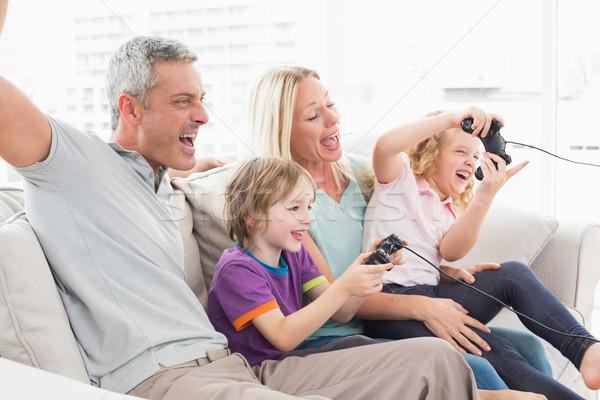 Famille jouer jeu vidéo séance canapé famille heureuse Photo stock © wavebreak_media