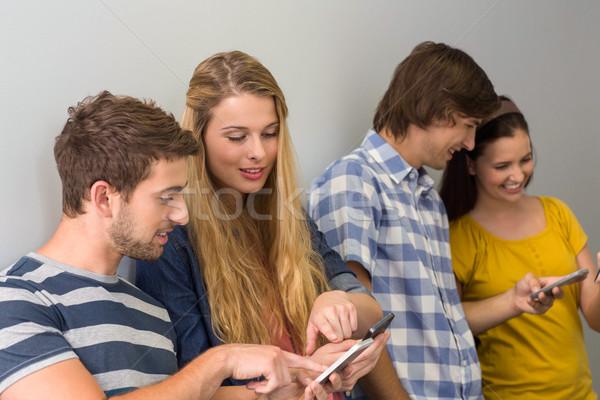 College students using cellphones Stock photo © wavebreak_media