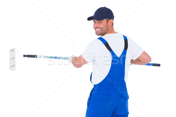 Handyman in overalls using paint roller on white background Stock photo © wavebreak_media