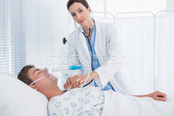 Smiling doctor auscultating her patients chest Stock photo © wavebreak_media