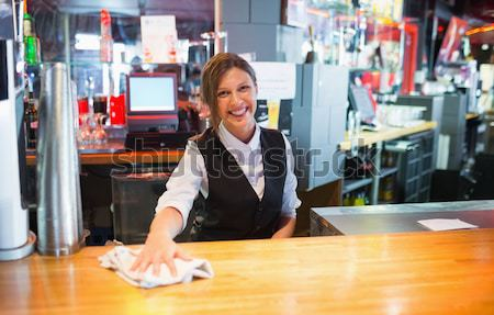 Happy barmaid writing in notepad Stock photo © wavebreak_media
