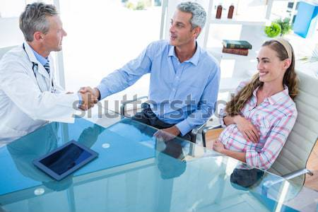 Pregnant woman and her husband discussing with doctor Stock photo © wavebreak_media