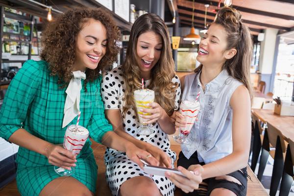 Női barátok megbeszél mobiltelefon ül étterem Stock fotó © wavebreak_media