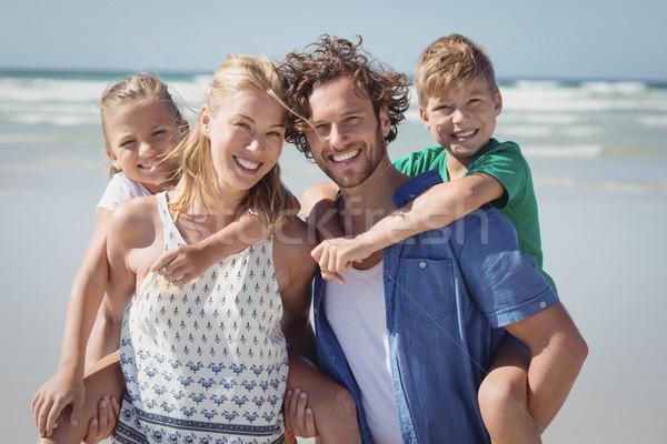 Portrait of happy family piggybacking at beach Stock photo © wavebreak_media