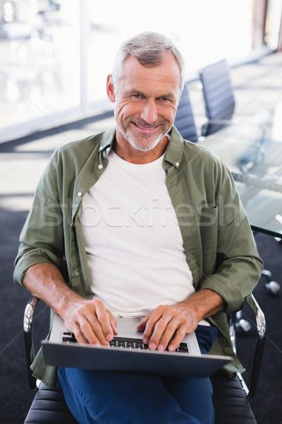Portrait of smiling businessman using laptop Stock photo © wavebreak_media