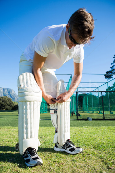 Cricket player wearing kneepad while standing on grassy field Stock photo © wavebreak_media