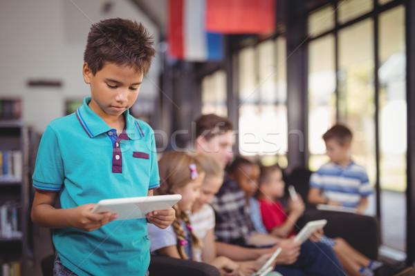 Attentive schoolboy using digital tablet in library Stock photo © wavebreak_media