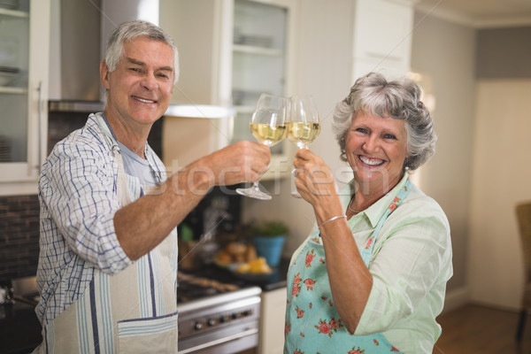 Stock photo: Portrait of smiling senior couple toasting wineglasses while standing in kitchen