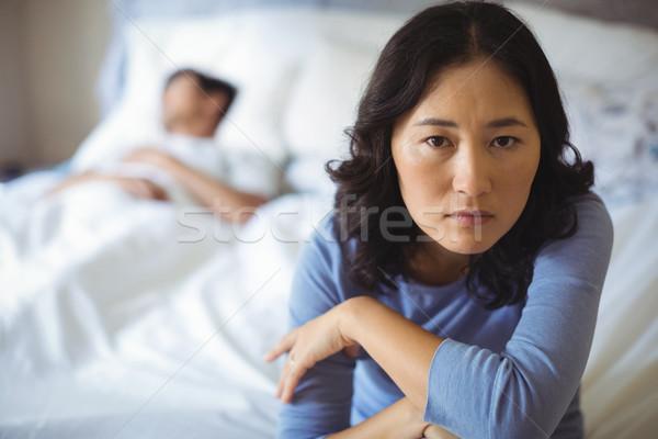 Upset woman sitting on bed in bedroom Stock photo © wavebreak_media