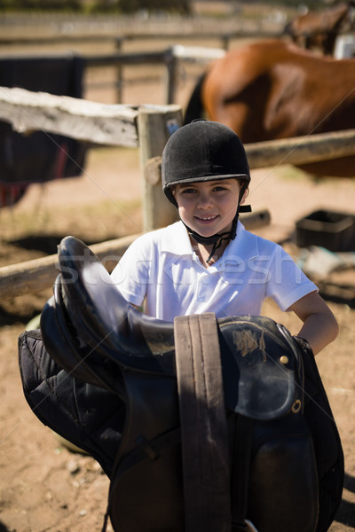 Smiling girl holding horse saddle in the ranch Stock photo © wavebreak_media