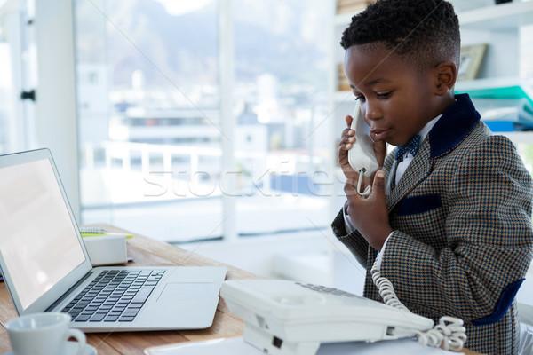 Smiling businessman with laptop using telephone at desk Stock photo © wavebreak_media