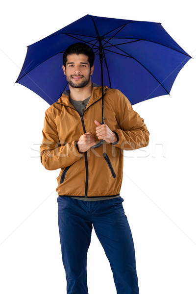 Smiling man standing under umbrella against white background Stock photo © wavebreak_media