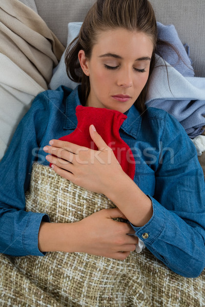 Directly above shot of woman with hot water bottle while sleeping on sofa at home Stock photo © wavebreak_media