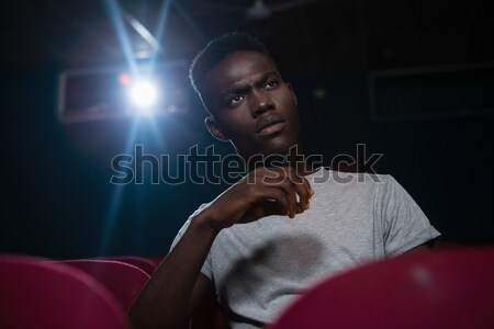 Man drinking cold drinks while watching movie in theatre Stock photo © wavebreak_media