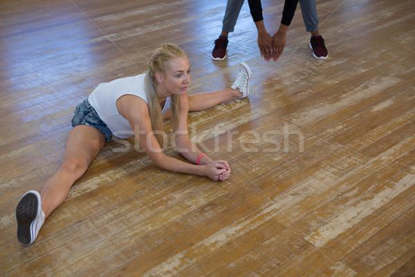 Full length of female dancer with friend stretching legs Stock photo © wavebreak_media