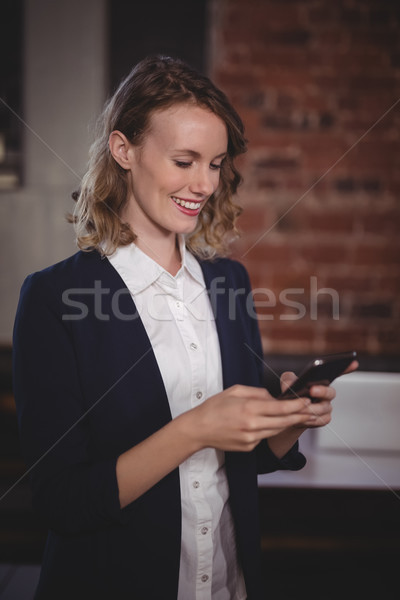 Smiling young beautiful female editor using smartphone at coffee shop Stock photo © wavebreak_media