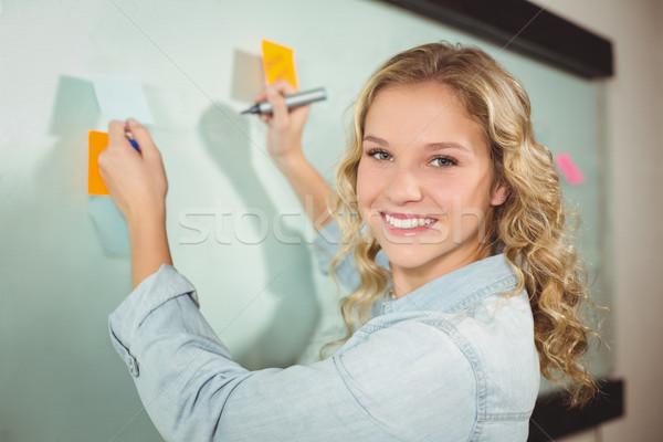 Portrait of beautiful woman holding sticky note while writing on Stock photo © wavebreak_media