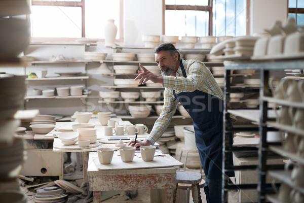 Male potter writing the orders in notebook Stock photo © wavebreak_media