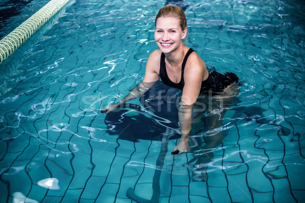 Smiling woman cycling in the swimming pool Stock photo © wavebreak_media