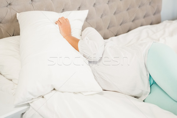 Pregnant woman covering face with pillow Stock photo © wavebreak_media