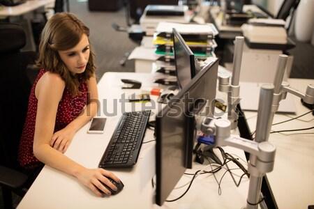 Female executive holding digital camera while looking at laptop Stock photo © wavebreak_media