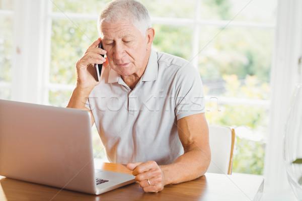 Konsantre kıdemli adam bakıyor dizüstü bilgisayar telefon Stok fotoğraf © wavebreak_media