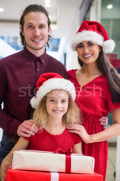 Family in Christmas attire standing with Christmas gifts Stock photo © wavebreak_media