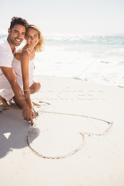Couple drawing heart on sand Stock photo © wavebreak_media