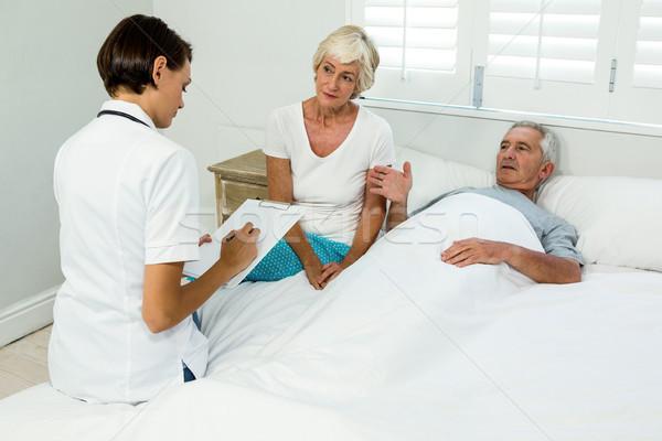 Female caregiver assisting senior man at home Stock photo © wavebreak_media