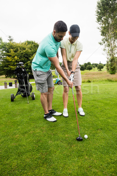 Male instructor assisting woman in learning golf Stock photo © wavebreak_media