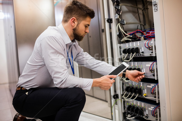 Stock photo: Technician using digital tablet while analyzing server