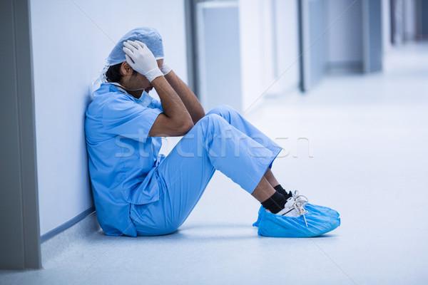 Smutne chirurg posiedzenia piętrze szpitala korytarz Zdjęcia stock © wavebreak_media