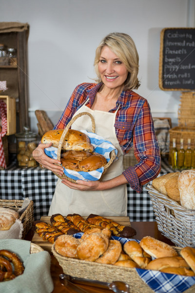 Smiling female staff holding wicker basket of breads at counter Stock photo © wavebreak_media