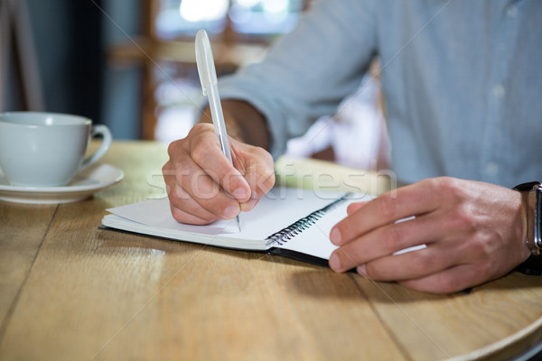Stock photo: Young man writing in diary at table in coffee shop