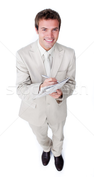 Stock photo: Charismatic young businessman holding a newspaper