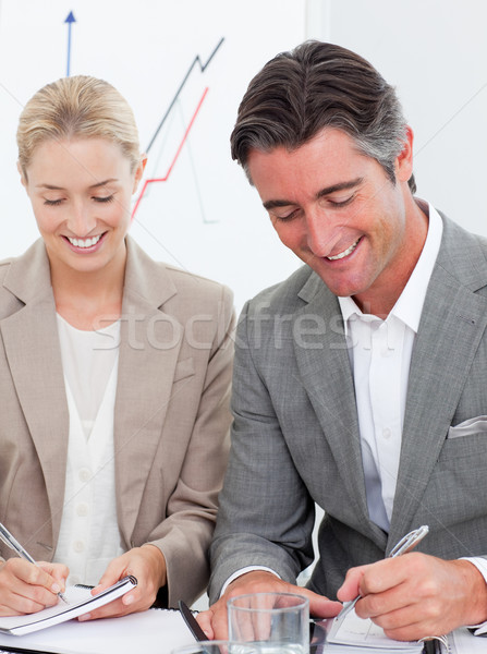 Cheerful business people writting notes in a meeting Stock photo © wavebreak_media