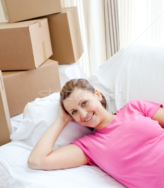 Happy woman relaxing on a sofa with boxes Stock photo © wavebreak_media