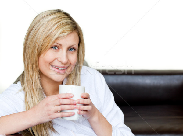 Self-assured woman holding a cup of coffee against a white background Stock photo © wavebreak_media