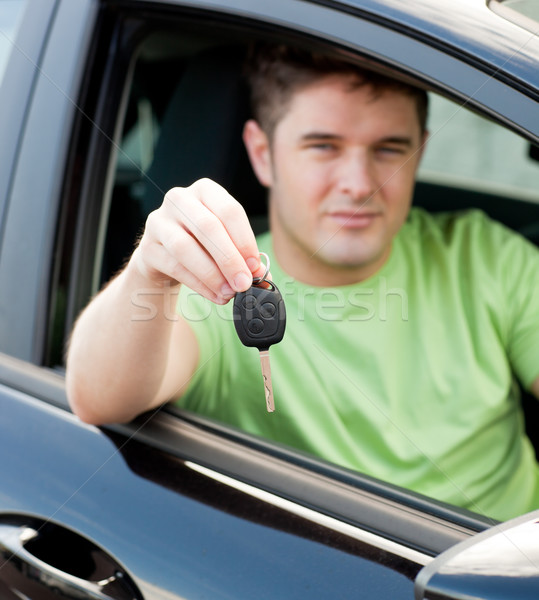 Happy young male driver sitting in blue car and holding his car key Stock photo © wavebreak_media