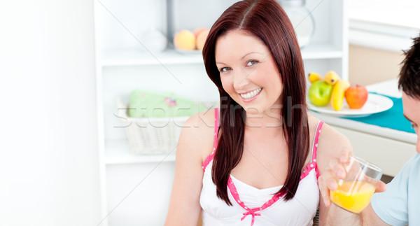 Pretty girlfriend smiling at the camera whils her boyfriend is drinking orange juice in the kitchen Stock photo © wavebreak_media