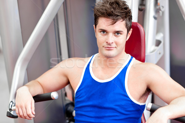 Self-assured young man using a bench press in a fitness center Stock photo © wavebreak_media