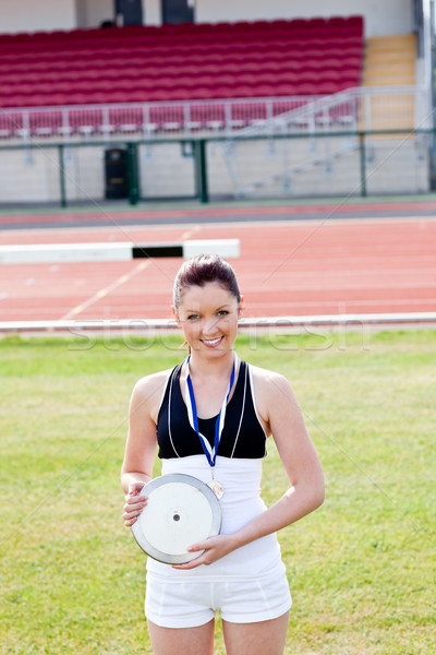 Smiling female athlete with a gold medal holding a disc in a stadium Stock photo © wavebreak_media