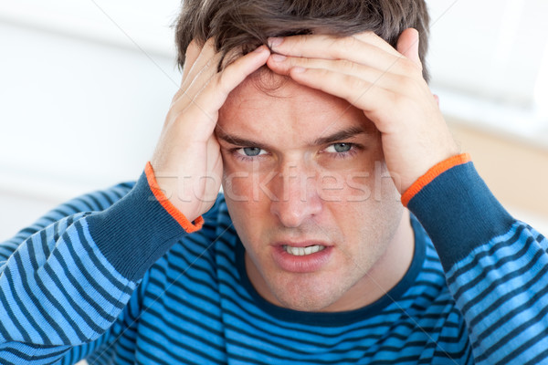 Caucasian man having a headache in the living-room at home Stock photo © wavebreak_media