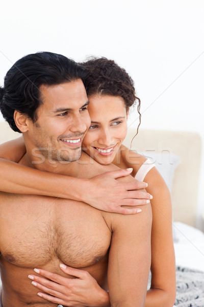 Passionate woman hugging her boyfriend sitting on their bed Stock photo © wavebreak_media